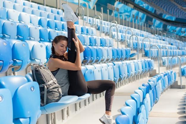 Sportliches junges mädchen, das auf dem sitz im stadion sitzt.