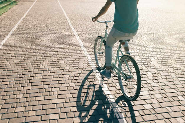 Sportliches junges mädchen, das fahrrad an einem sonnigen morgen fährt