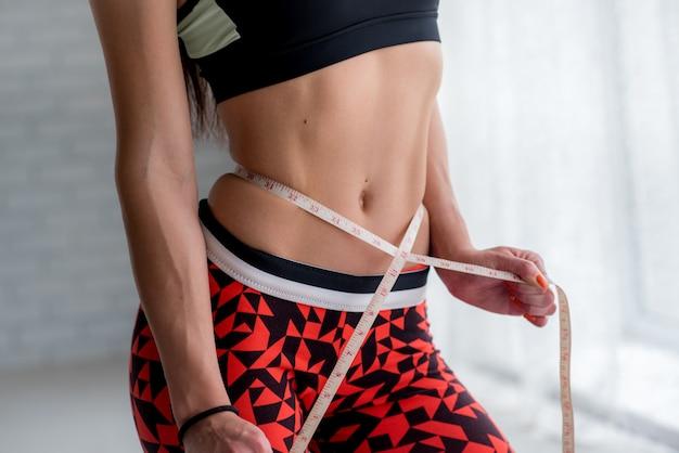 Sportliches junges mädchen misst ihre schlanke taille. gesunder lebensstil