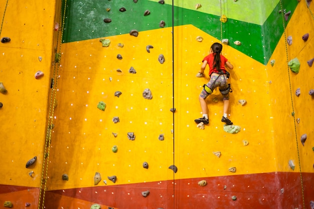 Sportliches kleines mädchen, das künstlichen felsbrocken auf praktischer wand im fitnessstudio klettert