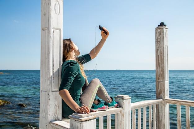 Sportliches mädchen am pier mit dem telefon