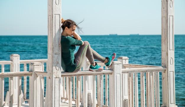 Sportliches mädchen auf dem pier, das übungen macht, um fitness zu tun
