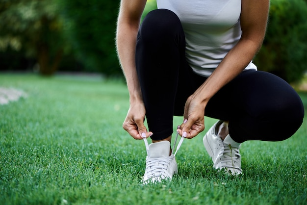 Sportliches mädchen bindet schnürsenkel im park vor einem lauf