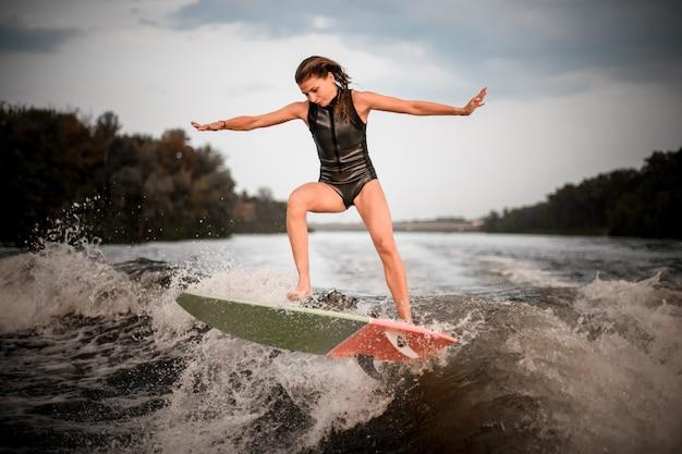 Sportliches mädchen, das auf das wakeboard auf dem fluss auf der welle springt
