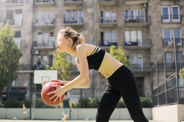 Sportliches mädchen, das basketball spielt