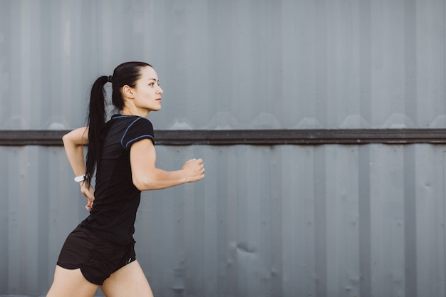 Sportliches mädchen, das in schwarz gekleidet ist, läuft auf grauem wandhintergrund