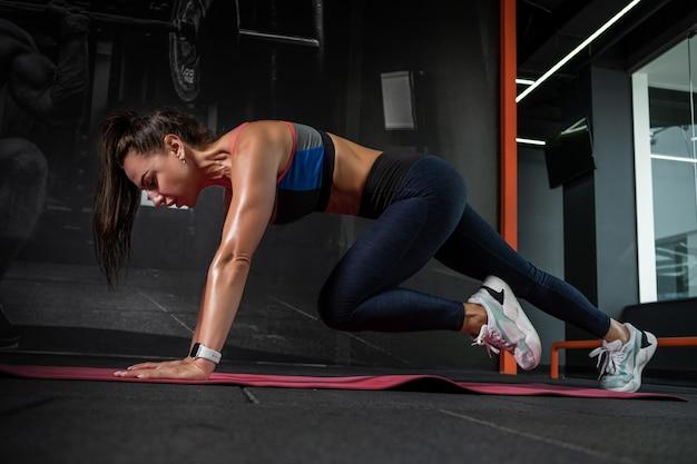 Sportliches mädchen, das kletterer-liegestütze auf der trainingsmatte im fitnessstudio macht