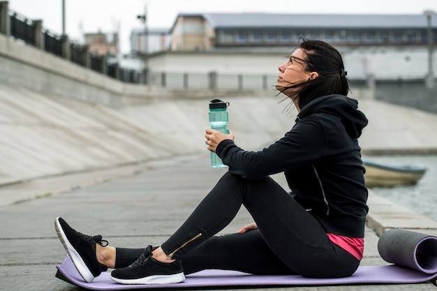 Sportliches mädchen, das mit flasche wasser sitzt