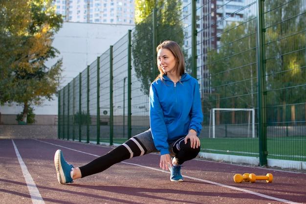 Sportliches mädchen, das sich auf einem laufband aufwärmt, turnerin, die draußen in der sportbekleidung arbeitet, kopiert raum