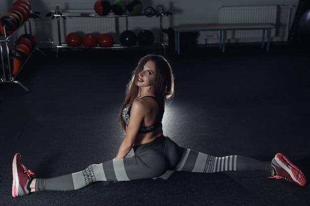 Sportliches mädchen, das sich im fitnessraum ausdehnt. aktiver lebensstil. fitness, bodybuilding. körperpflege, gesundheitswesen.