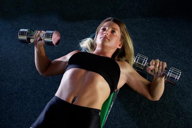 Sportliches mädchen, das übung mit hanteln im fitnessstudio tut