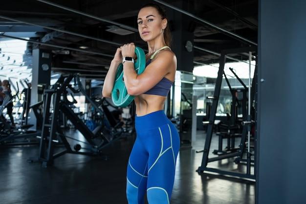 Sportliches mädchen, das übungen mit hantelscheibe im fitnessstudio durchführt