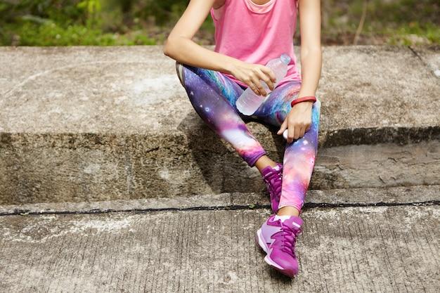 Sportliches mädchen im rosa trägershirt, leggings mit raumdruck und lila laufschuhen, die auf bordstein sitzen und wasser aus der plastikflasche nach cardio-training trinken. sportlerin, die während des trainings im freien hydratisiert