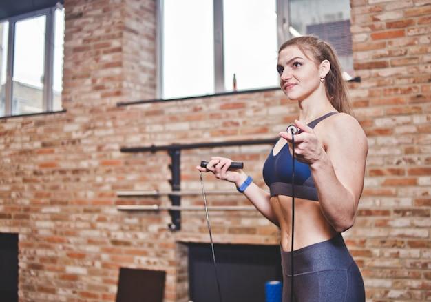 Sportliches mädchen im sportbekleidungsfrauen-training mit einem springseil im fitnessstudio. cardio training.