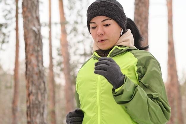 Sportliches mädchen in den ohrknospen, die ausatmen, während sie allein im winterwald laufen