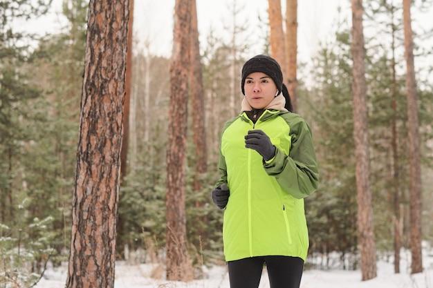 Sportliches mädchen in der grünen jacke, die allein im winterwaldpark beim training im freien läuft