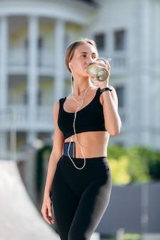 Sportliches mädchen in der schwarzen sportkleidung mit kopfhörern trinkt wasser.