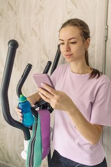 Sportliches mädchen in sportkleidung mit einer flasche wasser und telefoniert zu hause