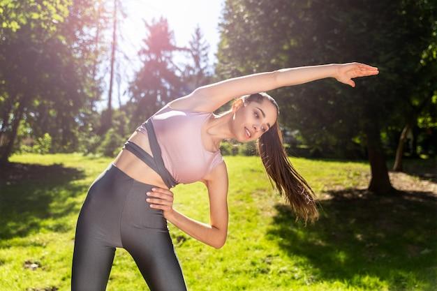 Sportliches mädchen mit einem pferdeschwanz, der im freien körperliche übungen tut