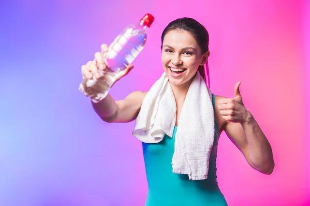 Sportliches mädchen mit flasche wasser und handtuch auf ihren schultern. foto des fitnessmodells lokalisiert auf weißem hintergrund. daumen hoch.