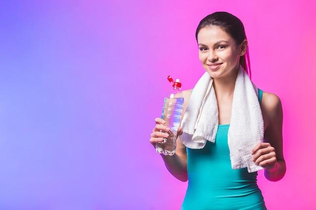 Sportliches mädchen mit flasche wasser und handtuch auf ihren schultern. foto des fitnessmodells lokalisiert auf weißem hintergrund.