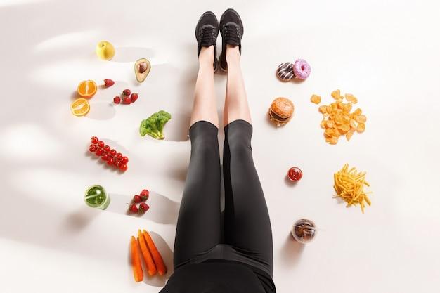 Sportliches mädchen mit gesundem essen auf boden