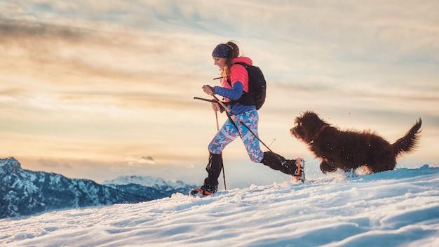 Sportliches mädchen mit ihrem hund während eines alpinen trekkings auf dem schnee