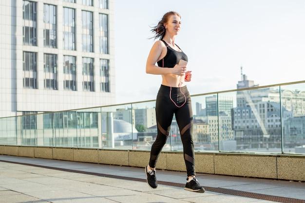 Sportliches mädchen rennt morgens zum training gegen die stadt und hört musik, sie lächelt und trainiert