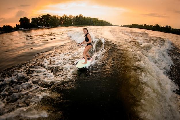 Sportliches mädchenreiten auf dem wakeboard auf dem fluss auf der welle des motorboots