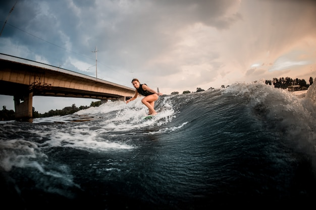 Sportliches mädchenreiten auf dem wakeboard auf dem fluss im hintergrund der brücke
