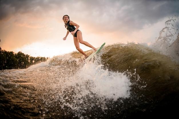 Sportliches mädchenreiten auf dem wakeboard auf dem fluss