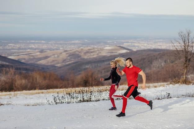 Sportliches paar, das am verschneiten wintertag zusammen in der natur läuft. beziehung, winterfitness, outdoorfitness