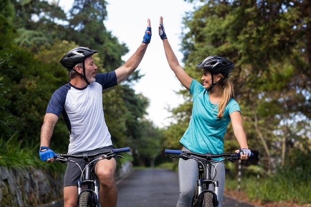 Sportliches paar, das hohe fünf beim fahrradfahren auf der straße gibt