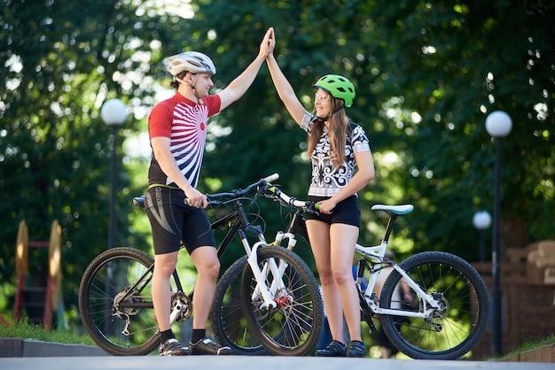 Sportliches paar, das hohe fünf im park gibt