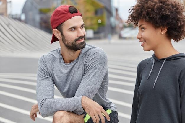 Sportliches paar, das in der außeneinstellung aufwirft