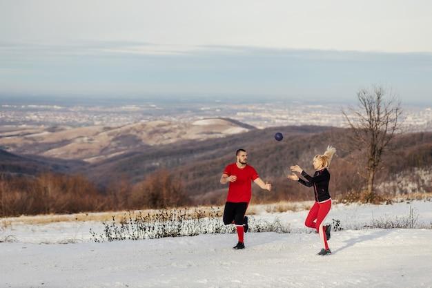 Sportliches paar, das in der natur am auffälligen wintertag läuft und übungen mit fitnessball macht. winter fitness, gesunde gewohnheiten, beziehung