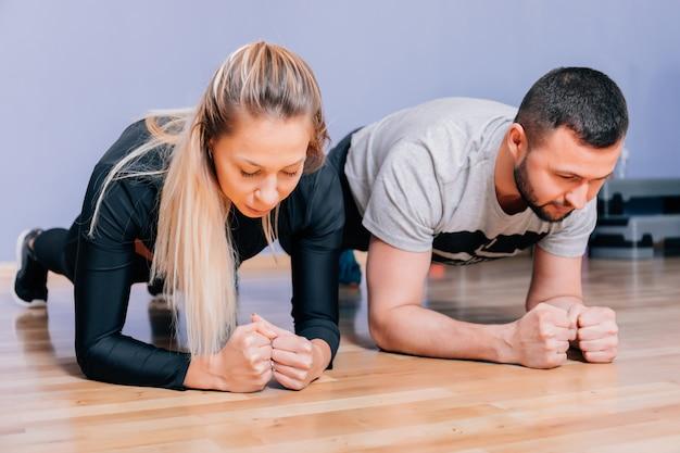 Sportliches paar, das plankenübung im fitnessstudio tut. porträt eines muskulösen paares, das beplankungsübungen macht.