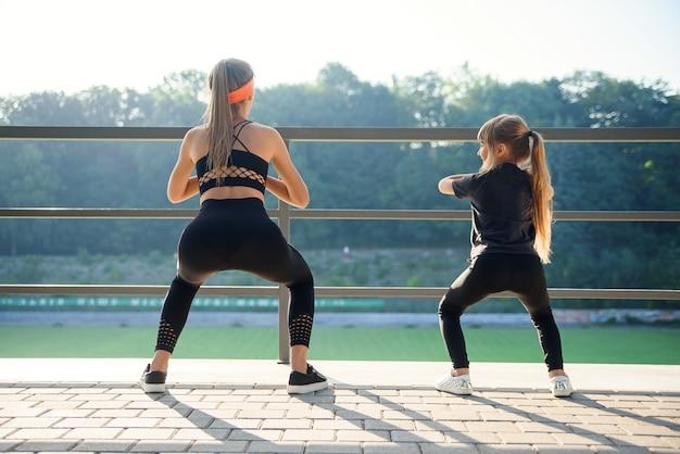 Sportliches paar, das sprungübung während des fitness-trainings im freiluftstadion tut