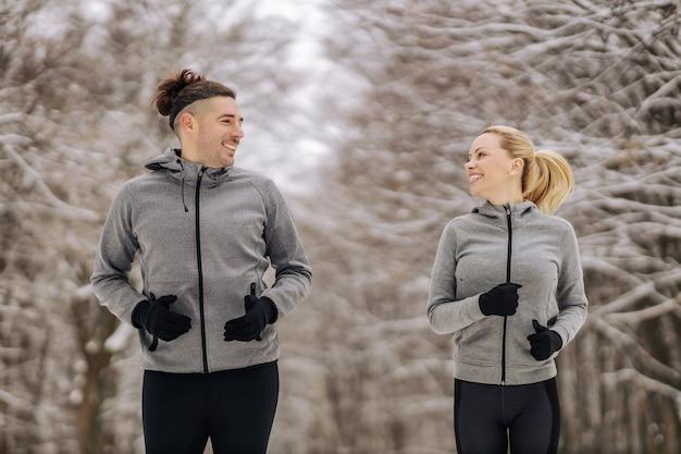 Sportliches paar, das zusammen am verschneiten wintertag in der natur läuft. outdoor fitness, winter fitness, gesunde gewohnheiten