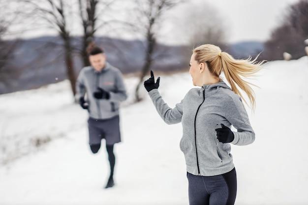Sportliches paar, das zusammen in der natur am wintertag auf schnee läuft.