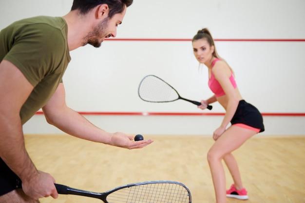 Sportliches paar, das zusammen squash spielt