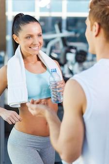 Sportliches paar im fitnessstudio. schöne junge sportliche paare, die beim stehen in der turnhalle sprechen und lächeln