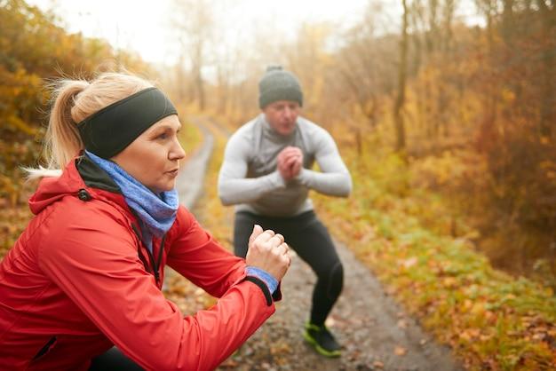 Sportliches paar macht kniebeugen im wald