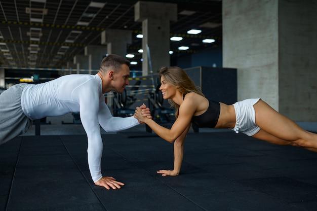Sportliches paar macht liegestütze, trainiert im fitnessstudio