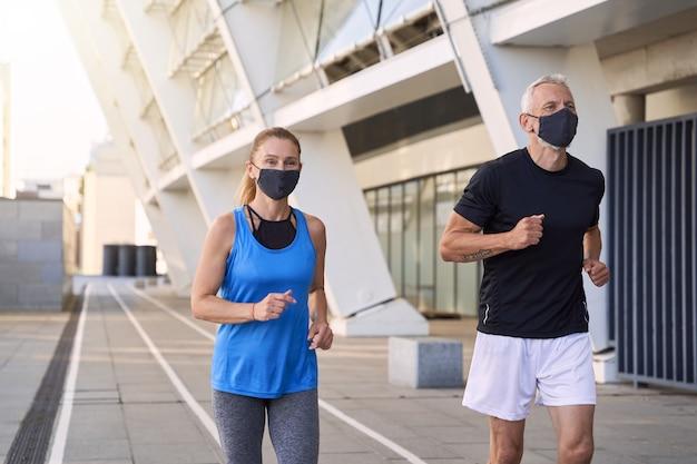 Sportliches reifes paar mit schützenden gesichtsmasken, die zusammen in der städtischen umgebung joggen