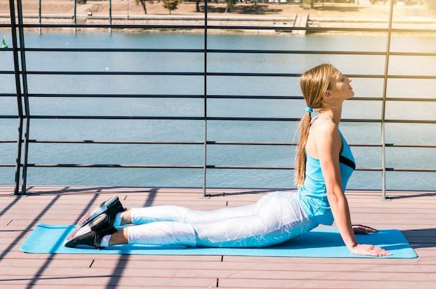 Sportliches schönes übendes yoga der jungen frau an draußen