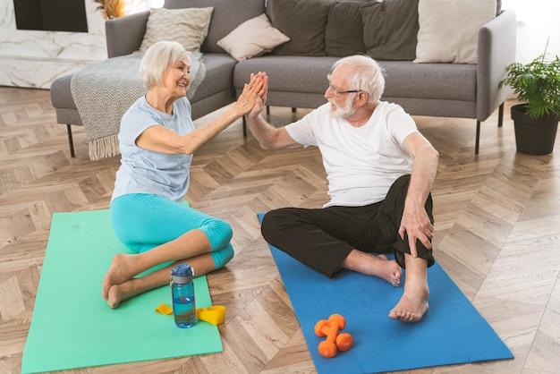 Sportliches seniorenpaar macht zu hause fitness- und entspannungsübungen - ältere menschen trainieren, um gesund und fit zu bleiben