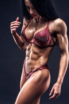 Sportliches sexy gebräuntes junges mädchen mit den großen bauchmuskeln