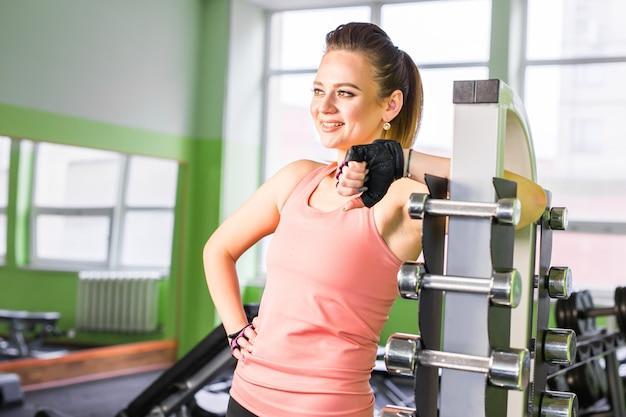 Sportliches sportlächelndes mädchen mit fitnessformkörper, der im fitnessstudio aufwirft und sich entspannt