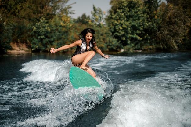 Sportliches surfgirl auf einem surfbrett nahe küste